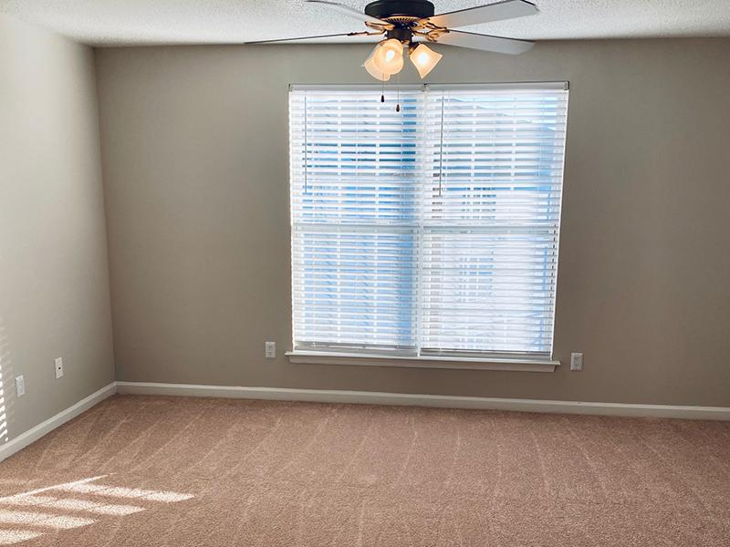 A carpeted room with a ceiling fan and window at The Lakes at Town Center Apartments.