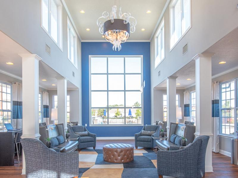 The resident lounge is decorated with upholstered chairs and couches at The Lakes at Town Center Apartments.