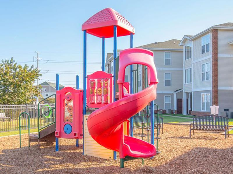A large slide and climbing equipment sit in the playground at The Lakes at Town Center Apartments.