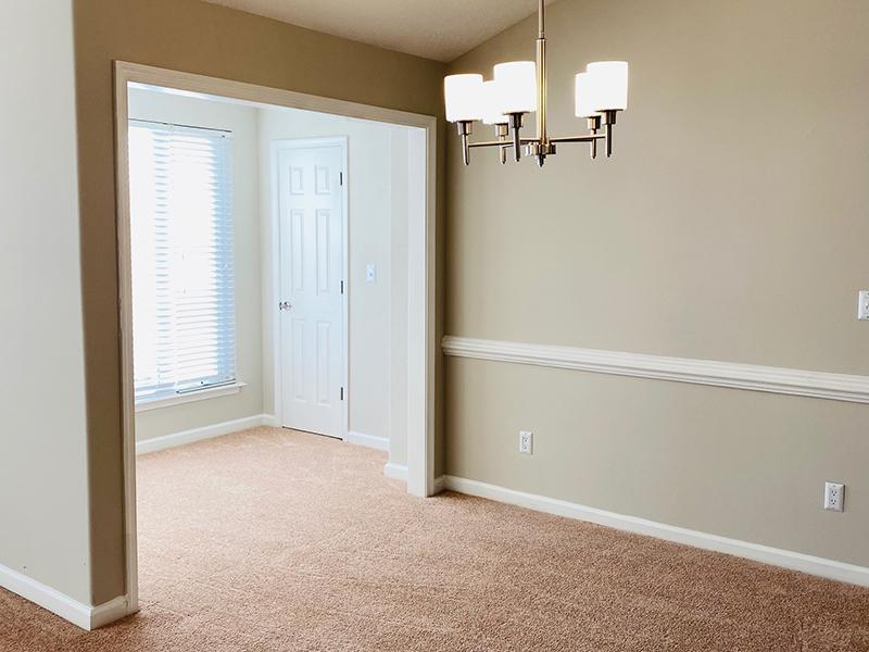 A chandelier hangs above a carpeted room in the apartments at The Lakes at Town Center in Hampton.