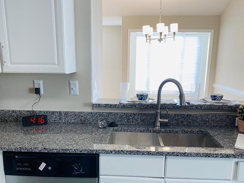 A double sink and granite-style countertops in the kitchens at The Lakes at Town Center Apartments.