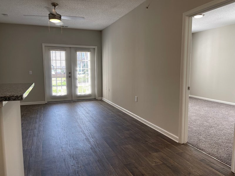 The living room leads to a carpeted bedroom in an apartment at The Lakes at Town Center.