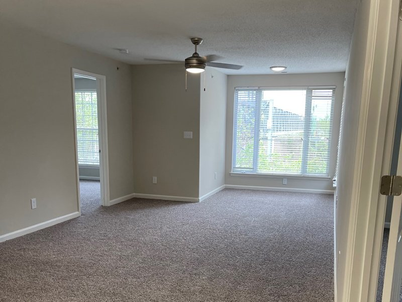 A carpeted room with double windows covered with blinds at an apartment in Hampton.