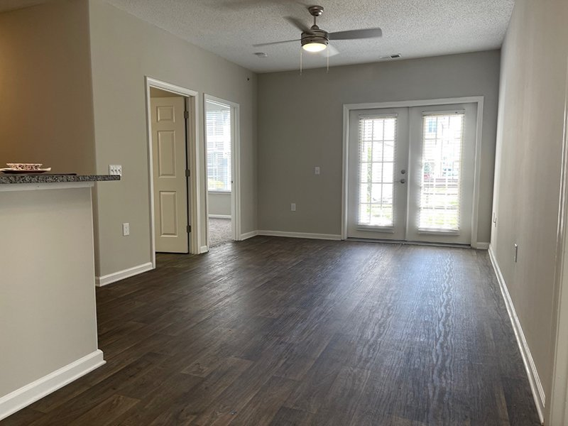 Model living room with wood-style flooring, a ceiling fan and sliding glass door in an apartment in Hampton.