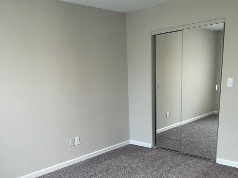 A bedroom with a mirrored closet at The Lakes at Town Center Apartments in Hampton.