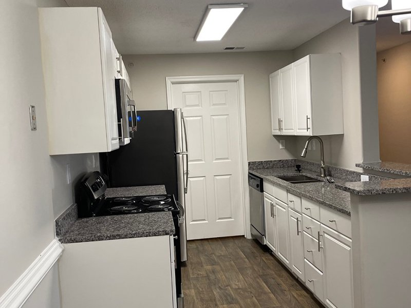 A galley style kitchen with modern appliances and a attached laundry room at The Lakes at Town Center Apartments.