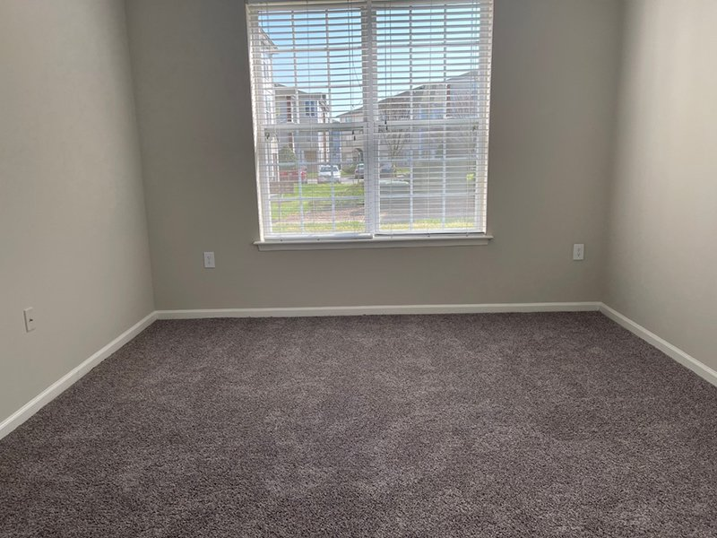 A large window with blinds in a bedroom at The Lakes at Town Center Apartments.