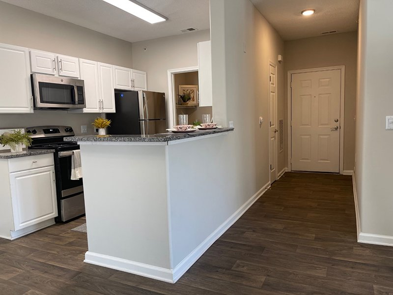 A breakfast bar overlooks the kitchen with stainless steel appliances at The Lakes at Town Center Apartments.