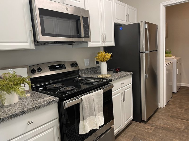 Modern stainless steel appliances and wood-style flooring furnish the kitchen in an apartment in Hampton.