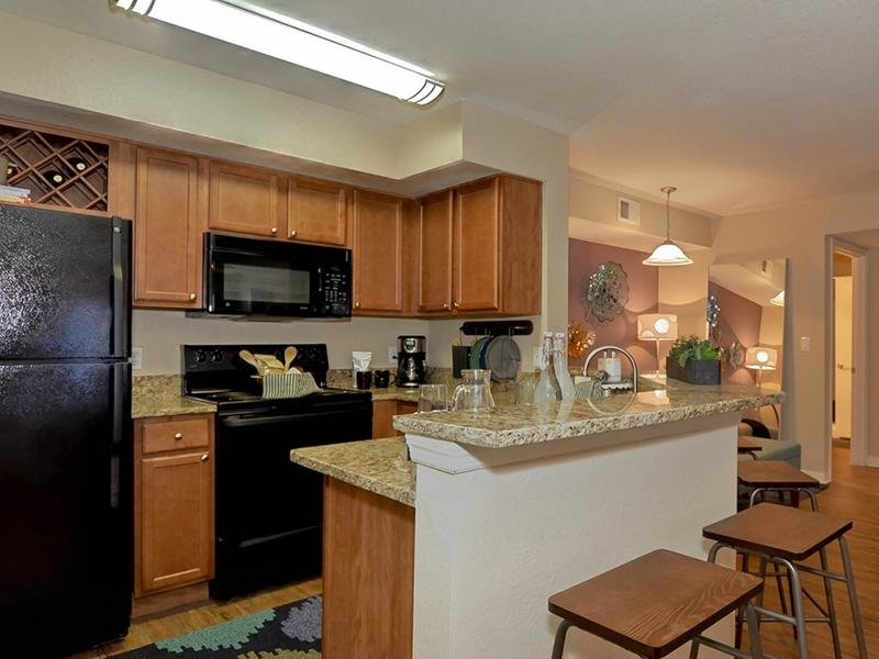 The kitchen has modern appliances and a breakfast bar in each apartment rental.