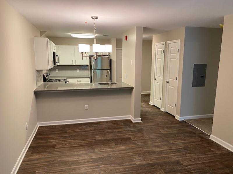 Large master bedroom with a bed, dresser, nightstands and attached bathroom at Retreat at Stonecrest Apartments.
