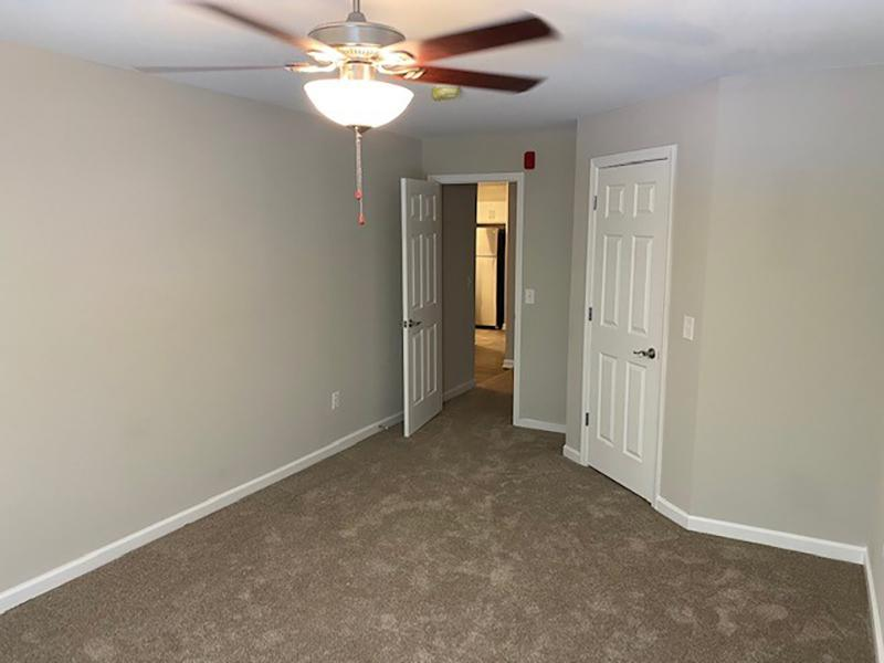 Carpeted bedroom with a large bed, dresser and nightstands at Retreat at Stonecrest Apartments in Lithonia, GA.