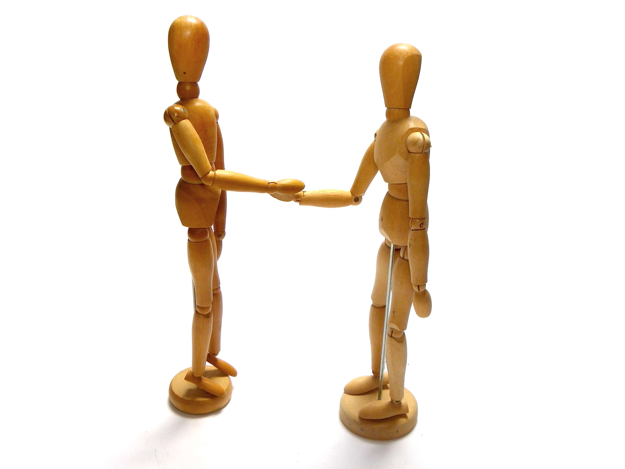Two wooden figures shaking hands