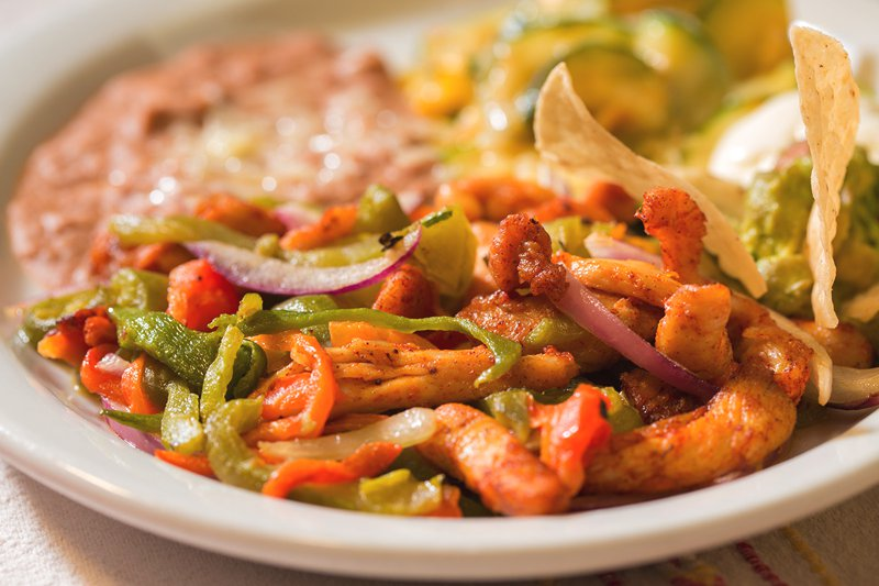 Chicken Fajitas: Marinated chicken breast sautéed with bell peppers and red onions