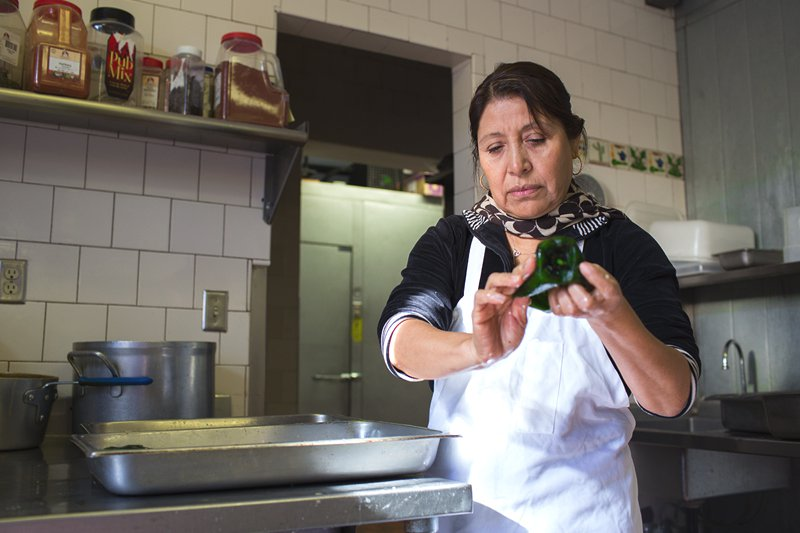 Teresa cleans poblano chiles for a fresh batch of Chicken Chile Rellenos