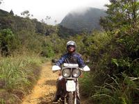Motorcycle rider travels on back roads through jungles of Sri Lanka