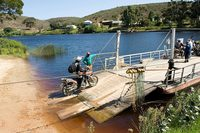 Motorcycle rider boards boat to cross river on South African adventure tour