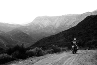 Black and white photo of motorcycle rider on dirt road