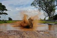 Dirt bike splashes through mud puddle on guided off-road motorbike tour in Sri Lanka