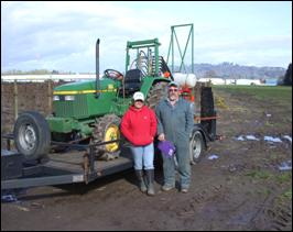 Two people pose in front of tractor loaded on a flatbed trailer.