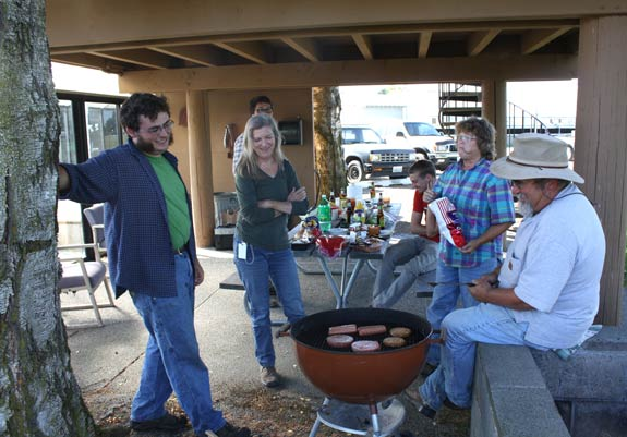 Entomology program staff gather around a charcoal grill during a summer BBQ.