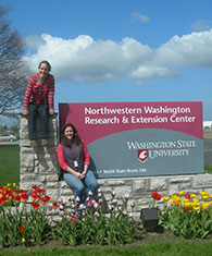 Two graduate students sit on the WSU NWREC sign.