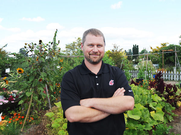 Bearded man stands with arms crossed in front of plants.