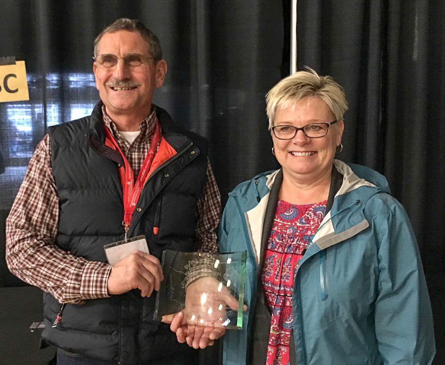 Randy Honcoop stands next to his wife, Leslie as he displays his 2017 Golden Berry Award.