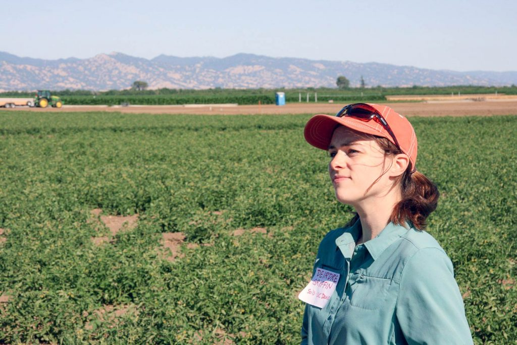 Deidre Griffin gazes out of frame with agricultural fields behind her.