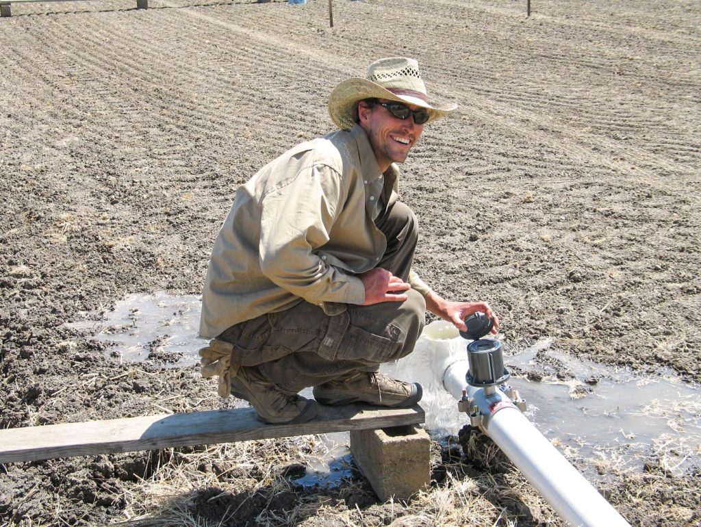 Gabe LaHue crouches to check an irrigation line in a plowed field.