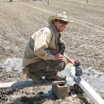 Man in a hat crouches at an irrigation pipe in a bare field.