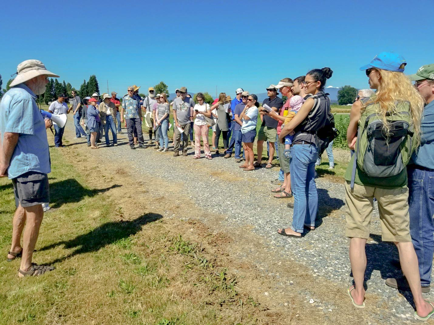 A group of attendees listen to a presentation during the annual NWREC Field Day.