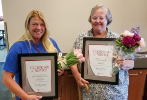 Two women holding flowers and framed certificates.