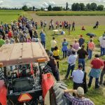 Tractor in foreground as large group listens to a field presentation.