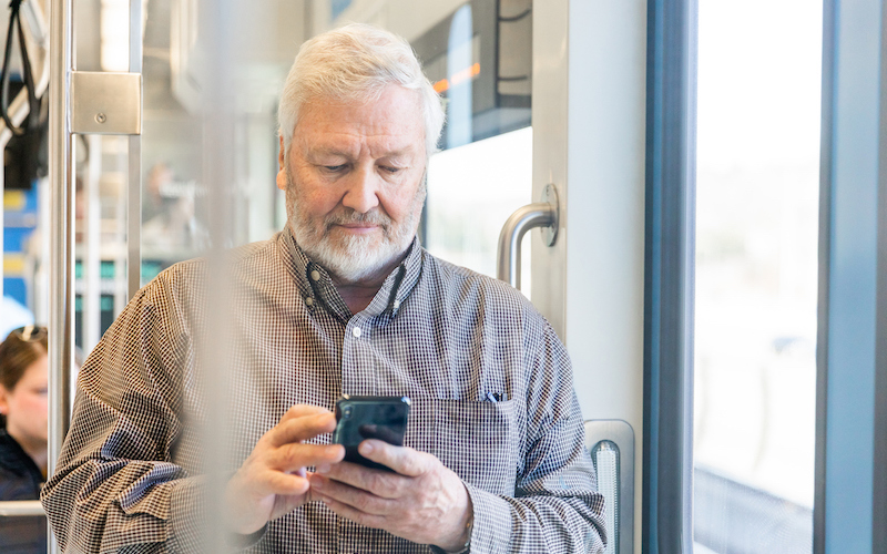 This image shows a community member completing an online survey on a mobile device while riding Link light rail.