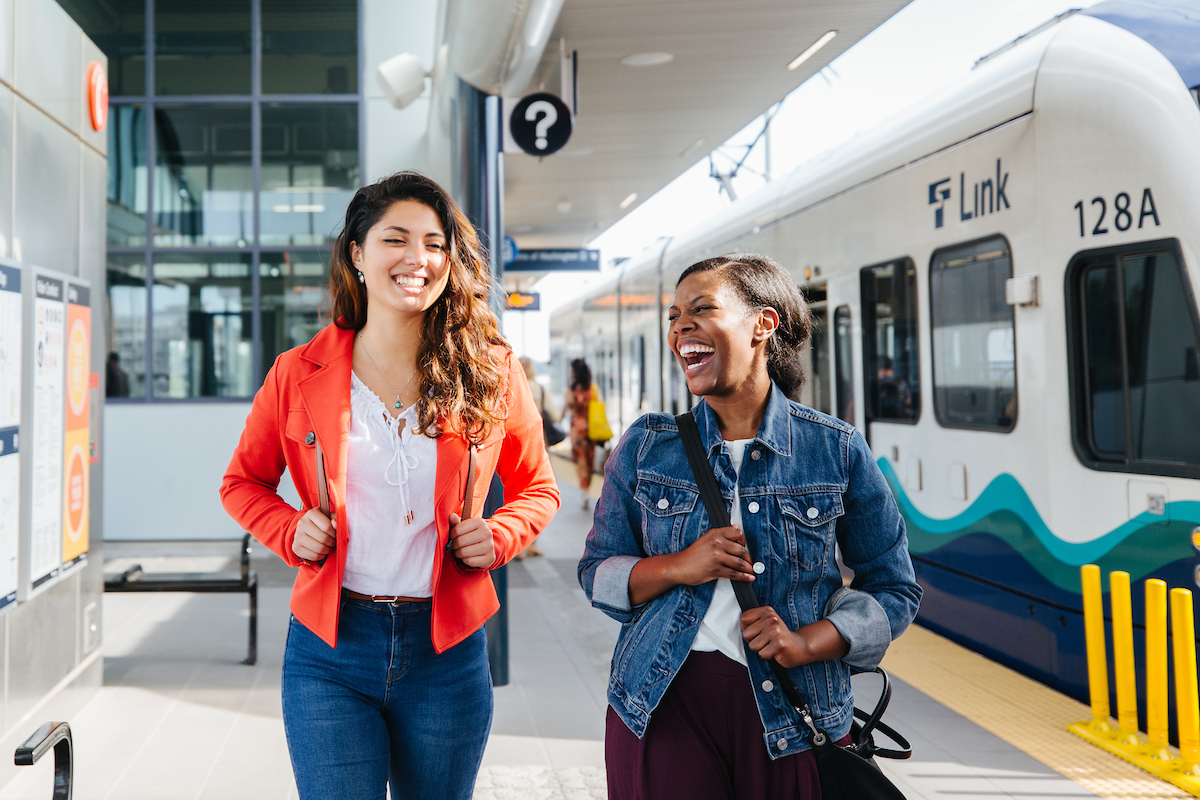 This image shows two community members talking and laughing on a light rail station platform.