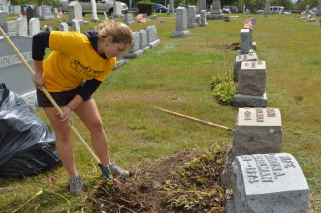 Dana Henninger of St. Paul's Evangelical Lutheran Church in Summit Hill digs at weeds Sunday during a volunteer cleanup day at GAR Cemetery in Summit Hill. JARRAD HEDES/TIMES NEWS