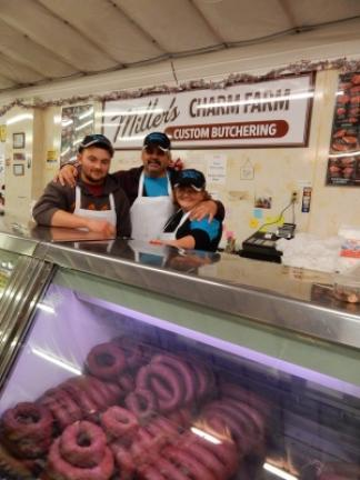 From left, Mark, Randy and Cathie Miller at Miller's Charm Farm Custom Butchering stand at the Mahoning Valley Farmer's Market. Not shown is Mark's twin, Kevin. STACEY SOLT/SPECIAL TO THE TIMES NEWS