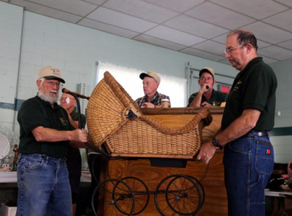Auction house employees, from left, Butch Wetzel, Gladwin Groff, Dean Arner and Henry Kriner sell a vintage Heywood Wakefield wicker perambulator on Saturday. DONALD R. SERFASS/TIMES NEWS