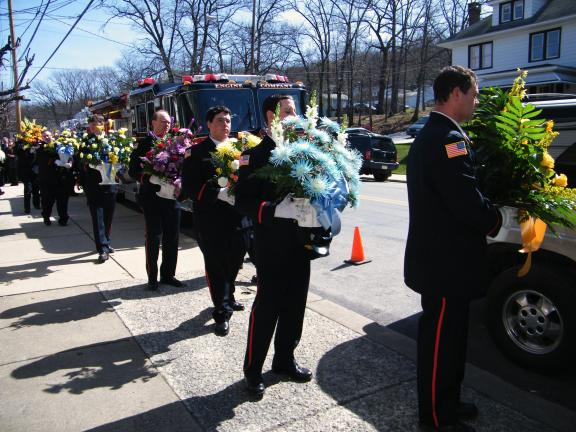 ANDREW LEIBENGUTH/SPECIAL TO THE TIMES NEWS Firefighters carry floral arrangements from the funeral home in tribute to Thomas Hartz Sr.