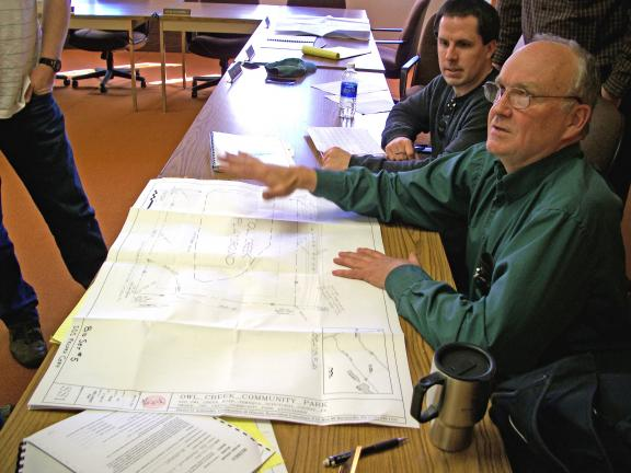 DONALD R. SERFASS/TIMES NEWS Dan Schroeder, Tamaqua community development director, explains details of the proposed Owl Creek playground at a bid opening meeting Wednesday at borough hall. On hand to provide additional information was, seen in…