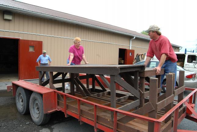 Ron Gower/TIMES NEWS Ray Zimmerman, right, of Pittman, Schuylkill County, positions tables onto his trailer after removing them from the Mahoning Farmers' Market in Mahoning Township. The farmers' market, which served generations of patrons, has…