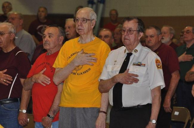Members of the various teams cover their hearts during the singing of the national anthem at the opening ceremony for the 22nd annual Carbon County Senior Games. From left are, Fred Nasarenko of the Jim Thorpe team; Bob Perkins of the Panther Valley…