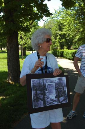 Betsy Burnhauser shows the members of a tour around the park a picture of the chain bridge memorial.