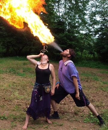 AL ZAGOFSKY/SPECIAL TO THE TIMES NEWS Mr. E breathes a fireball on the hilt of a sword swallowed by Riley Schillaci at the Midsummer Renaissance Faire.