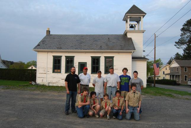 RON GOWER/TIMES NEWS Boy Scout Troop 145 has made the one-room, New Mahoning school house, owned by Mahoning Valley Fire Company, as their new headquarters. Scout members kneel in front while standing behind them are volunteers working to restore…