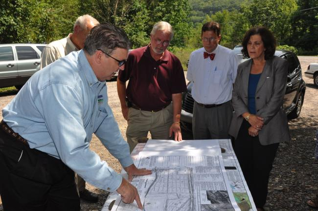 AMY ZUBEK/TIMES NEWS Members of the Carbon County Redevelopment Authority listen as John F. Curtis III, founder and CEO of Green Energy Capital Partners, front left, talks about the proposed solar park in Nesquehoning. Members of the authority, are,…