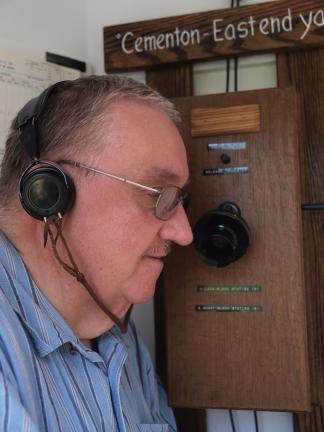 AL ZAGOFSKY/SPECIAL TO THE TIMES NEWS Railroad historian Mike Bednar demonstrates how the Block Phone was used when it was introduce a century ago. The phone user wore a headset to free his hands for writing.