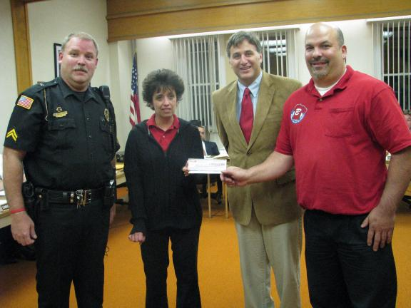 Liz Pinkey/times news Corporal Dwayne Hacker, left, and Mayor Christian Morrison, second from right, accept $500 from Boyer's Market to be used for drug enforcement activities in the community. Making the presentation were Shelly Young, second from…
