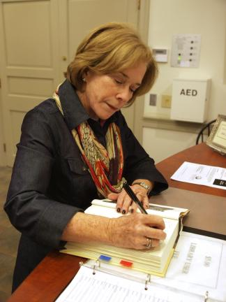 """AL ZAGOFSKY/SPECIAL TO THE TIMES NEWS Kate Buford signs a copy of her book, """"Native American Son,"""" owned by the Dimmick Memorial Library in Jim Thorpe."""